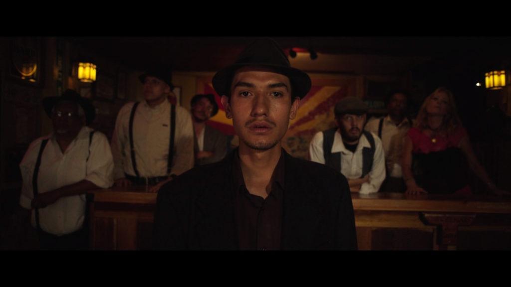 Reenactor in the film Bisbee 17, man standing in front of the Arizona flag