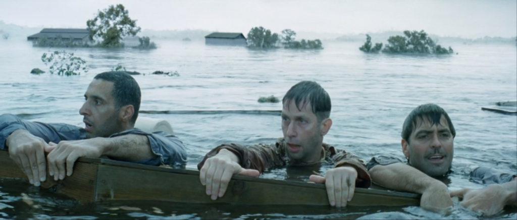 Three men hold onto a coffin as they float in a flooded valley, still from O Brother Where Art Thou