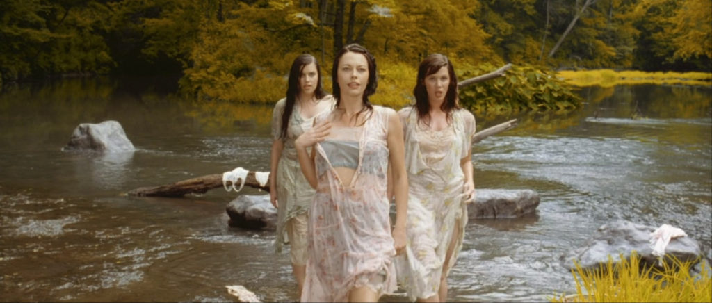 Three women in white dresses stand in a river, still from O Brother Where Art Thou