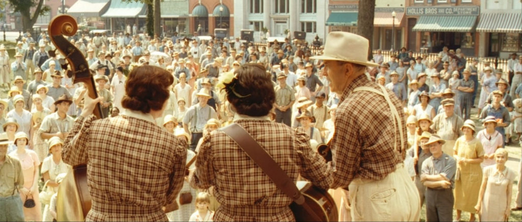 View of the back of three musicians facing an audience, still from O Brother Where Art Thou