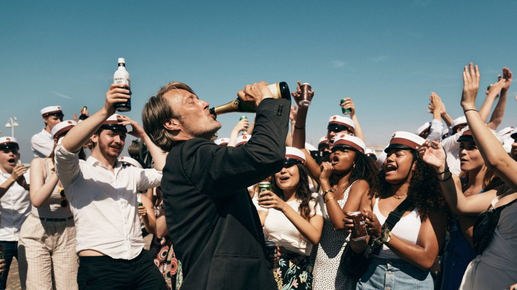 Still from the film Another Round, profile of a man drinking from a champagne bottle with a crowd of young people behind him