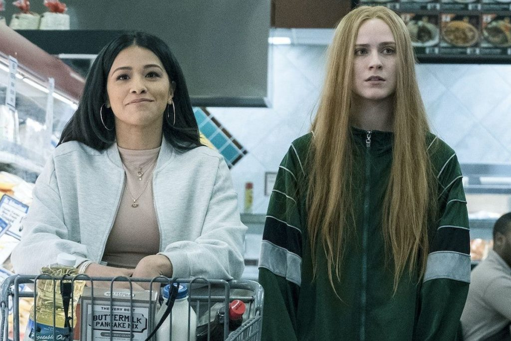 Still from the film Kajillionaire, a woman in a white jacket pushes a shopping cart and another woman walks beside her both facing the camera