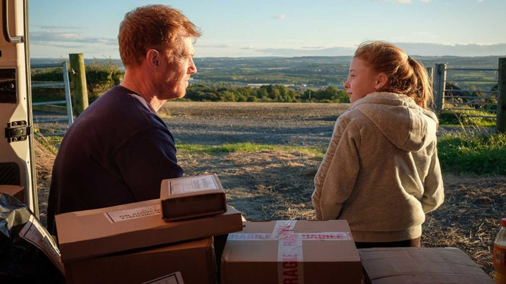 Still from the film Sorry We Missed You, a man sits in the back of a delivery truck with a young girl